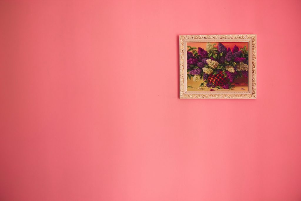 Framed painting on the top right corner of a pink wall