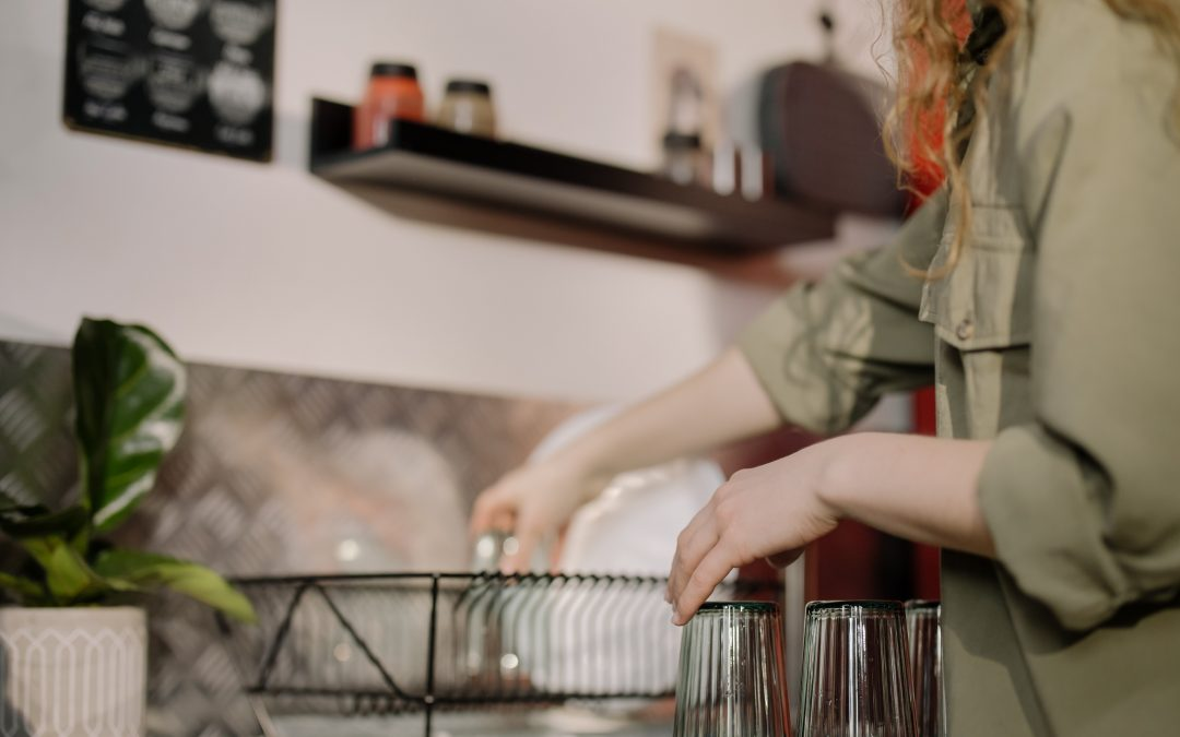 Woman in gray shirt puts dishes in disk rack to dry