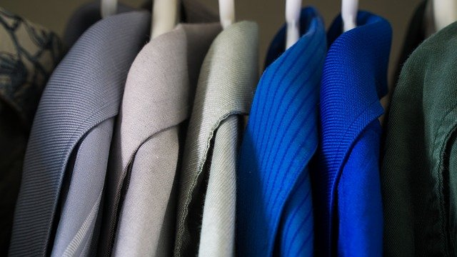 Collars of blue clothes hanging in organized closet.
