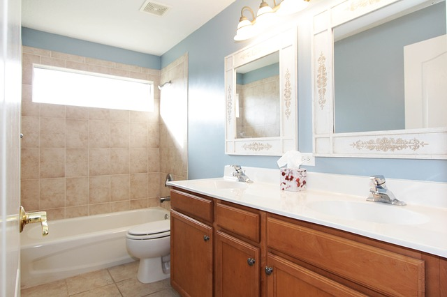 Bathroom with double sink and two framed mirrors
