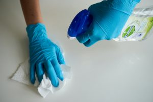 Two gloved hands wiping down a countertop with spray cleaner and a paper towel.